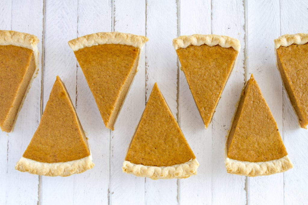 7 slices of homemade pumpkin pie in row sitting on white wooden table